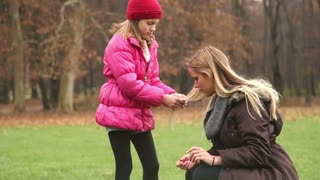 Beautiful little girl playing with her mother's long hair in park
