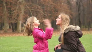 Beautiful little girl putting her hands through her mother's long hair in park
