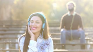 Beautiful woman and handsome man listening to music on headphones at the park, graded