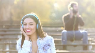 Beautiful woman and handsome man listening to music on headphones at the park, slow motion, graded