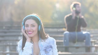 Beautiful woman and handsome man listening to music on headphones at the park, slow motion