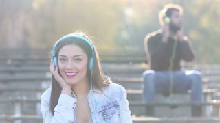 Beautiful woman and handsome man listening to music on headphones at the park