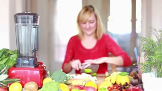 Beautiful Woman cutting apple in pieces for smoothie, in slow motion, graded