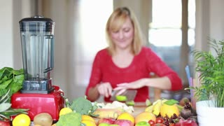 Beautiful Woman cutting apple in pieces for smoothie, in slow motion