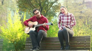 Beautiful woman singing while handsome man playing guitar, sitting next to her on bench in park, in slow motion, graded