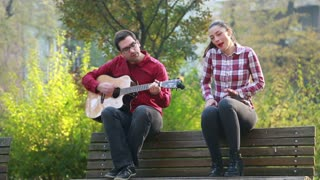 Beautiful woman singing while handsome man playing guitar, sitting next to her on bench in park, in slow motion