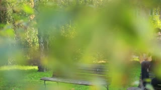 Beautiful woman singing while handsome man playing guitar, sitting next to her on bench in park, slow motion