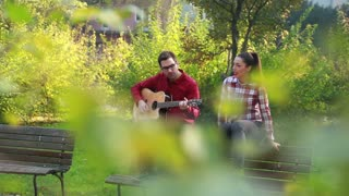 Beautiful woman singing while handsome man playing guitar, sitting next to her on bench in park