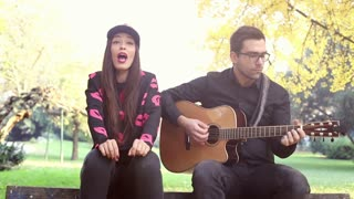 Beautiful woman singing while handsome man playing guitar sitting on park bench, graded