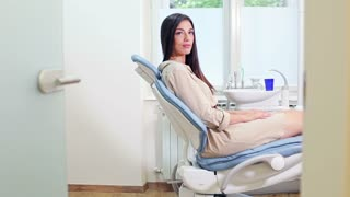 Beautiful woman sitting in dental chair and waiting for dentist to come