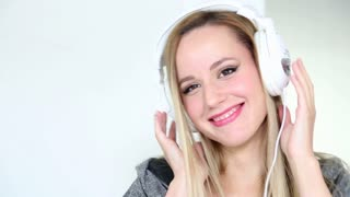 Beautiful young blond woman dancing with white headphones in white bright background