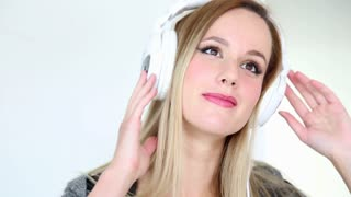 Beautiful young blond woman dancing with white headphones