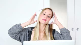 Beautiful young blond woman listening to music on laptop with white headphones