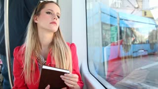 Beautiful young blond woman riding tram, holding the book