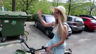 Beautiful young blonde girl riding bike on the street