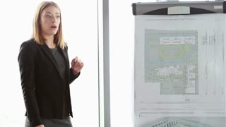 Beautiful young businesswoman giving presentation to colleagues during meeting at office