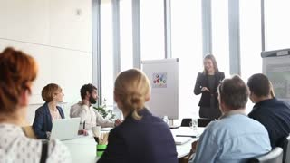 Beautiful young businesswoman giving presentation to colleagues