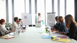 Beautiful young businesswoman pointing at flipchart on a meeting with colleagues