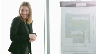 Beautiful young businesswoman smiling while giving presentation to colleagues during meeting at office, slow motion, graded