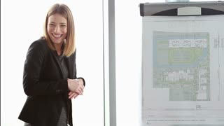 Beautiful young businesswoman smiling while giving presentation to colleagues during meeting at office, slow motion