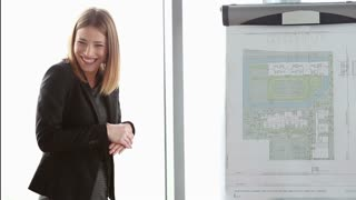 Beautiful young businesswoman smiling while giving presentation to colleagues during meeting at office