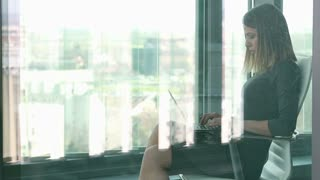 Beautiful young businesswoman typing on laptop while sitting on chair behind glass wall, graded