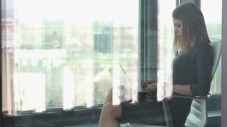 Beautiful young businesswoman typing on laptop while sitting on chair behind glass wall