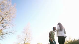 Beautiful young couple listening to music on headphones and dancing at the park, graded