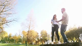 Beautiful young couple listening to music on headphones and dancing at the park, slow motion, graded
