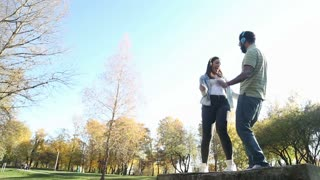 Beautiful young couple listening to music on headphones and dancing at the park, slow motion