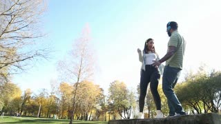 Beautiful young couple listening to music on headphones and dancing at the park