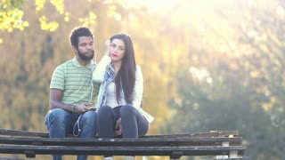 Beautiful young couple listening to music together, sharing earphones at the park, graded