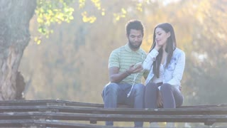 Beautiful young couple listening to music together, sharing earphones at the park