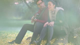 Beautiful young couple playing guitar and singing while sitting on a tree in park