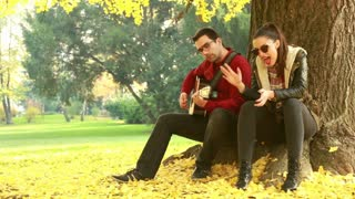 Beautiful young couple singing and playing guitar while sitting on a tree in park, graded