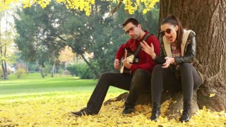 Beautiful young couple singing and playing guitar while sitting on a tree in park