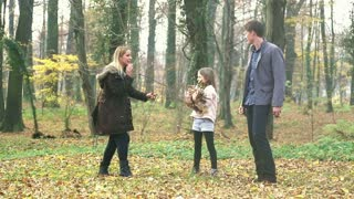 Beautiful young family having fun together, throwing leaves at each other in park, graded