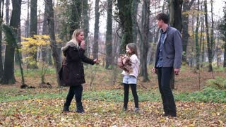 Beautiful young family having fun together, throwing leaves at each other in park