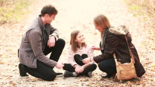 Beautiful young family sitting on pathway and playing games, enjoying in park in autumn, graded