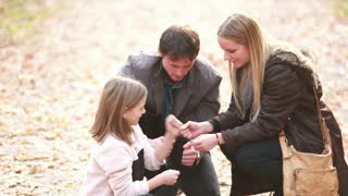 Beautiful young family sitting on pathway and playing games, enjoying in park in autumn, slow motion