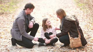 Beautiful young family sitting on pathway and playing games, enjoying in park in autumn