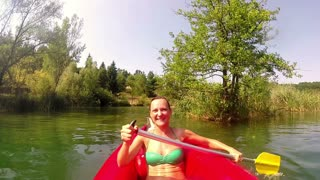 Beautiful young girl paddling canoe, smiling and waving to camera, graded, in slow motion