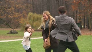 Beautiful young parents having fun with their cute daughter in nature, playing and laughing