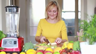 Beautiful young woman cutting banana into slices for fruit shake