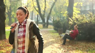 Beautiful young woman dancing while handsome man playing guitar in background, sitting on park bench, in slow motion, graded