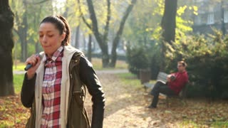 Beautiful young woman dancing while handsome man playing guitar in background, sitting on park bench, in slow motion