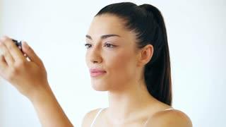 Beautiful young woman putting on mascara