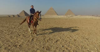 Beautiful young woman riding horse at Giza pyramids complex, Egypt