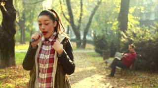 Beautiful young woman singing in park while handsome man playing guitar in background, sitting on park bench, graded