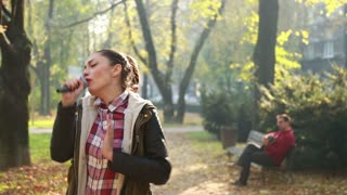 Beautiful young woman singing in park while handsome man playing guitar in background, sitting on park bench